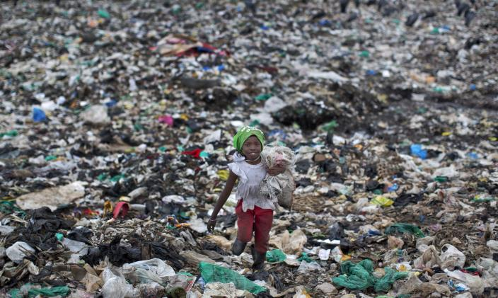 FILE - In this Thursday, Nov. 12, 2015 file photo, Joyce Njeri, 8, carries a torn sack holding the plastic bottles she has scavenged, as she walks amidst garbage and plastic bags at the garbage dump in the Dandora slum of Nairobi, Kenya, before a ban on plastic bags came into force in Kenya in 2017. The oil industry in 2020 has asked the United States to pressure Kenya to change its world-leading stance against the plastic waste that litters Africa, according to environmentalists who fear the continent will be used as a dumping ground. (AP Photo/Ben Curtis, File)