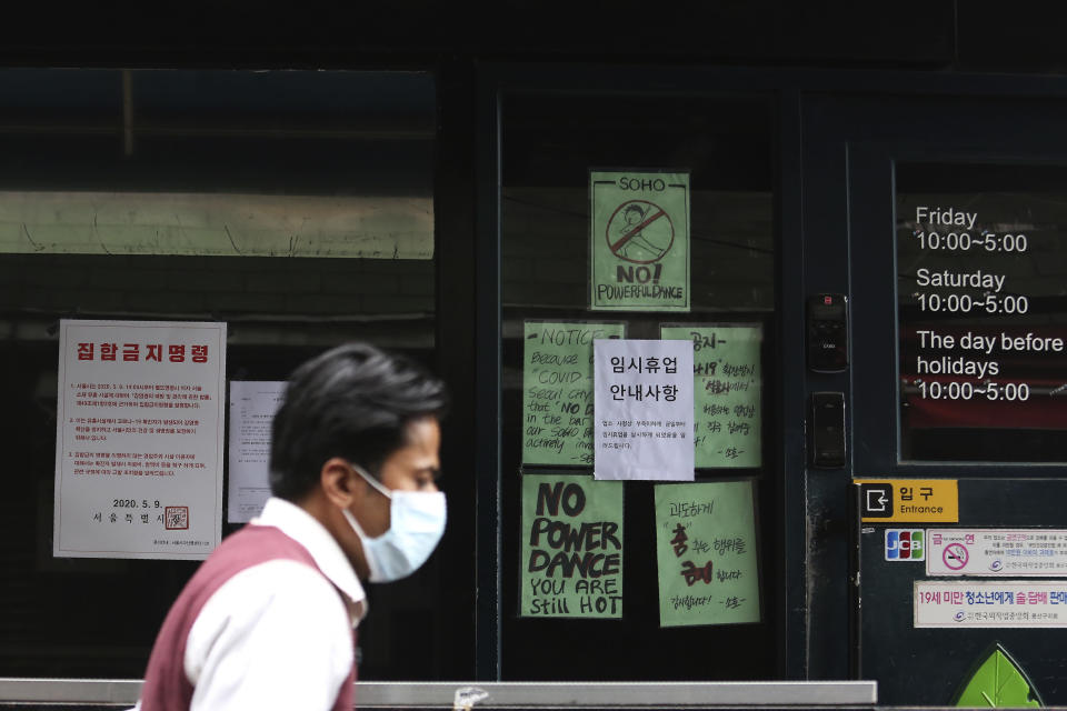 """A man waring a face mask passes by notices at the entrance of a temporary closed dance club in Seoul, South Korea, Sunday, May 10, 2020. South Korea on Friday advised nightclubs and similar entertainment venues to close for a month and may delay the reopening of schools after linking more than a dozen new coronavirus infections to clubgoers in the capital. The signs read """" Temporary closed,"""" right and """"the Seoul city emergency administrative order to prohibit gathering,"""" left. (AP Photo/Ahn Young-joon)"""