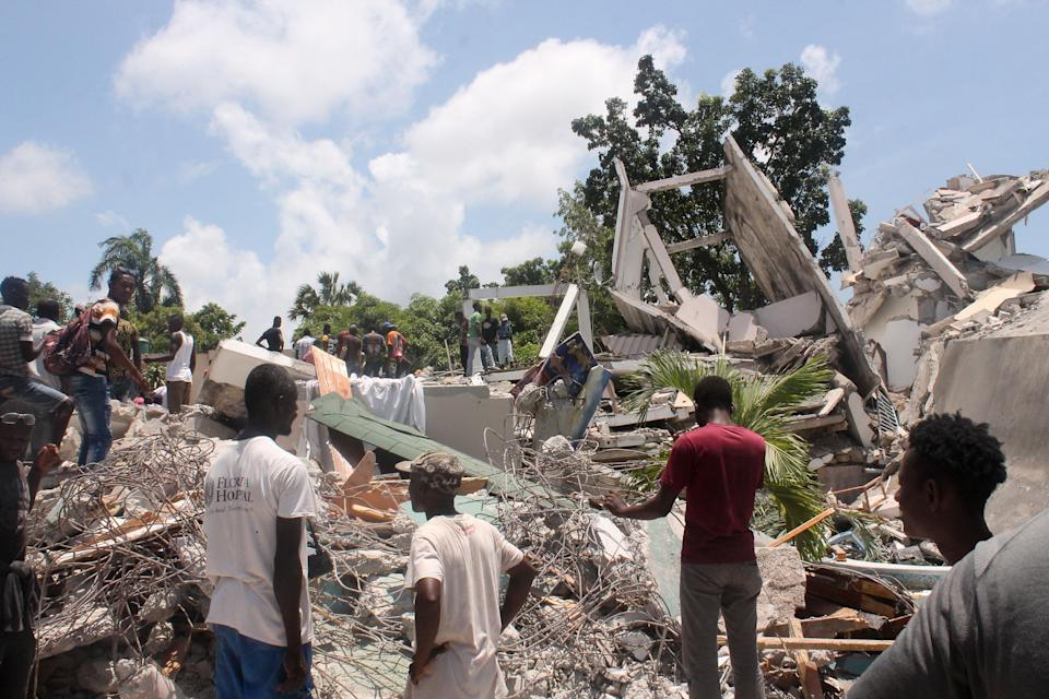 People search through the rubble of what used to be the Manguier Hotel after the earthquake hit on August 14, 2021 in Les Cayes, southwest Haiti.