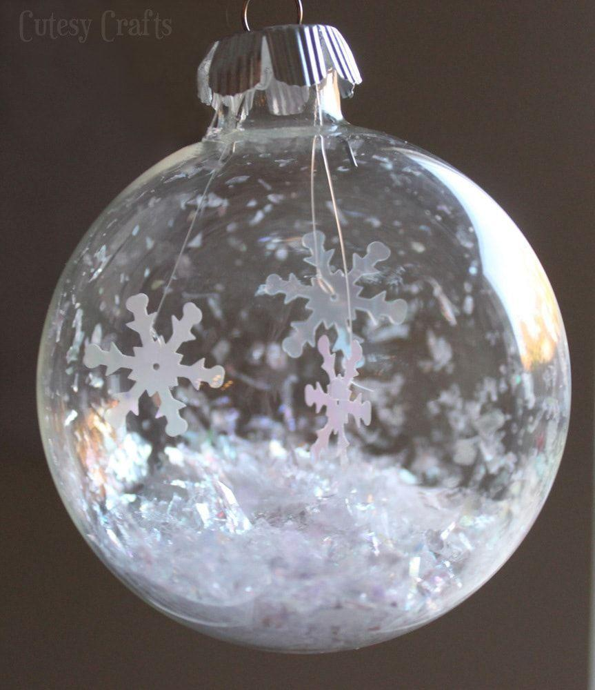"""<p>Shiny snowflake sequins hang inside glass ball ornaments for such a dainty wintry look. Use them to trim your tree, or hang them from ribbons to dress up wrapped presents.</p><p><a href=""""https://cutesycrafts.com/2013/12/glass-ball-snowflake-ornament.html"""" rel=""""nofollow noopener"""" target=""""_blank"""" data-ylk=""""slk:Get the tutorial at Cutesy Crafts"""" class=""""link rapid-noclick-resp""""><em>Get the tutorial at Cutesy Crafts</em></a></p>"""