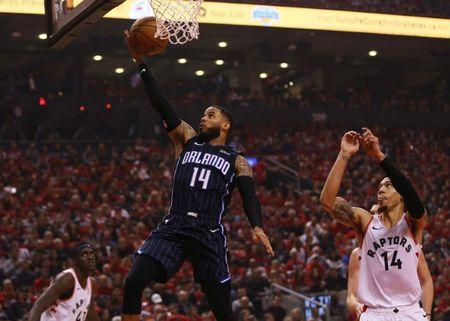Apr 13, 2019; Toronto, Ontario, CAN; Orlando Magic guard D.J. Augustin (14) goes up to make a basket as Toronto Raptors guard Danny Green (14) looks on during game one of the first round of the 2019 NBA Playoffs at Scotiabank Arena. Orlando defeated Toronto. Mandatory Credit: John E. Sokolowski-USA TODAY Sports