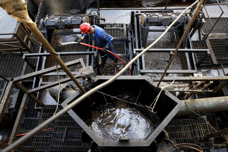 The flow of drilling mud is seen in a container while an oilfield worker works on a drilling rig at an oil well operated by Venezuela's state oil company PDVSA, in the oil rich Orinoco belt, near Cabrutica at the state of Anzoategui