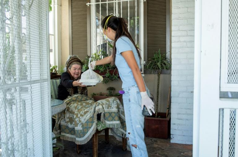 "Mira Kwon, the 16 year-old high school student who launched the Los Angeles branch of ""Zoomers to Boomers"", delivers groceries to Mary Navarro, an elderly disabled woman -- the service is now available in more than a dozen US cities (AFP Photo/VALERIE MACON)"