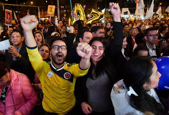 Colombians in Bogota celebrate on August 24, 2016 as they watch the signing of a peace agreement between the government and FARC guerrillas broadcast from Havana, Cuba (AFP Photo/Guillermo Legaria)