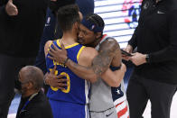 Golden State Warriors guard Stephen Curry, left, and Washington Wizards guard Bradley Beal, right, hug after an NBA basketball game, Wednesday, April 21, 2021, in Washington. The Wizards won 118-114. (AP Photo/Nick Wass)