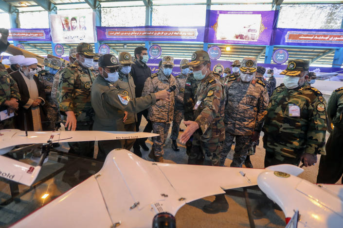 In this photo released Tuesday, Jan. 5, 2021 by the Iranian army, Chief of the General Staff of the Armed Forces Gen. Mohammad Hossein Bagheri, center, listens to an explanation while visiting at a display of drones prior to a drill, Iran. The Iranian military on Tuesday began a wide-ranging, two-day aerial drill in the country's north, state media reported, featuring combat and surveillance unmanned aircraft, as well as naval drones dispatched from vessels in Iran's southern waters. (Iranian Army via AP)