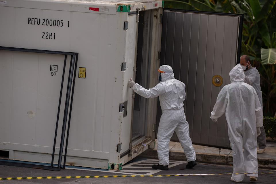 Health workers wear protective suits as they leave a body of a victim of the novel coronavirus in a refrigerated container at the Vinte Oito de Agosto Public Hospital, a unit treating COVID-19 patients in Manaus, Amazonas State, Brazil, on January 4, 2021. - The coronavirus has killed at least 1,843,631 people worldwide since the outbreak emerged in China in December 2019, according to an AFP tally on Monday based on official sources. The US is the worst-affected country with 351,590 deaths, followed by Brazil with 196,018. (Photo by Michael DANTAS / AFP) (Photo by MICHAEL DANTAS/AFP via Getty Images)