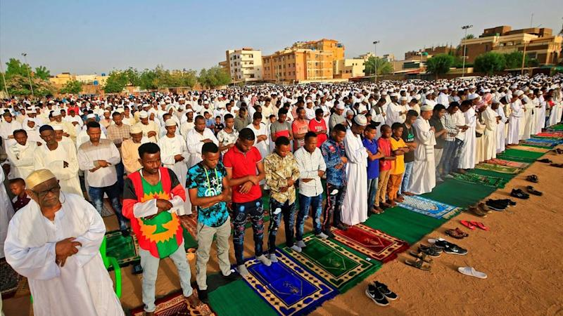 "Muslim worshippers gather for the prayers of Eid al-Fitr, the Muslim holiday which starts at the conclusion of the holy fasting month of Ramadan, in the district of Jureif Gharb of Sudan""s capital Khartoum early on May 24, 2020, despite government regulations banning congregations due to the COVID-19 coronavirus pandemic."