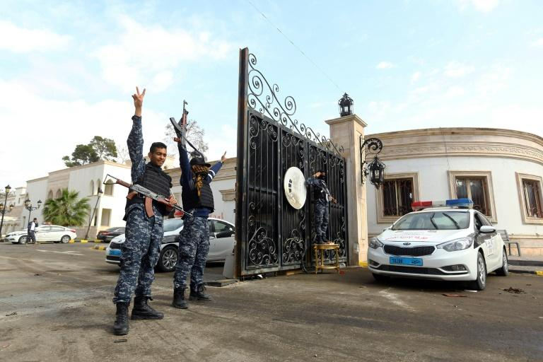 Libyan security forces flash victory signs outside the Guest Palace, a complex of luxury villas in central Tripoli on March 15, 2017