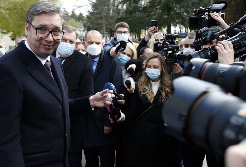 Serbian President Aleksandar Vucic poses with a vial of the Sputnik V in Belgrade, Serbia, Thursday, April 15, 2021. Serbia has announced it will begin packing and later producing Russia's Sputnik V coronavirus vaccine, which would make it the first European state outside Russia and Belarus to begin manufacturing the jab. (AP Photo/Darko Vojinovic)