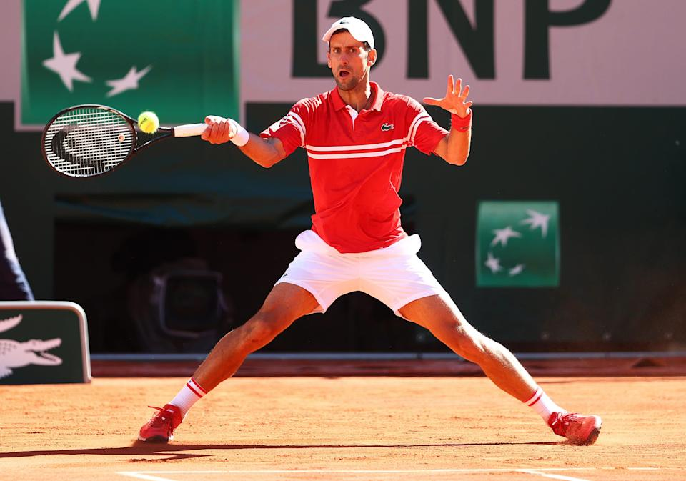 Novak Djokovic returns a forehand in the French Open men's final against Stefanos Tsitsipas on the clay courts at Roland Garros.