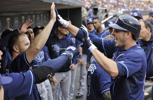 Tampa Bay Rays' Matt Joyce, right, celebrates in the dugout after his solo home run off Minnesota Twins pitcher Nick Blackburn in the first inning of a baseball game Saturday, Aug. 11, 2012 in Minneapolis. (AP Photo/Jim Mone)
