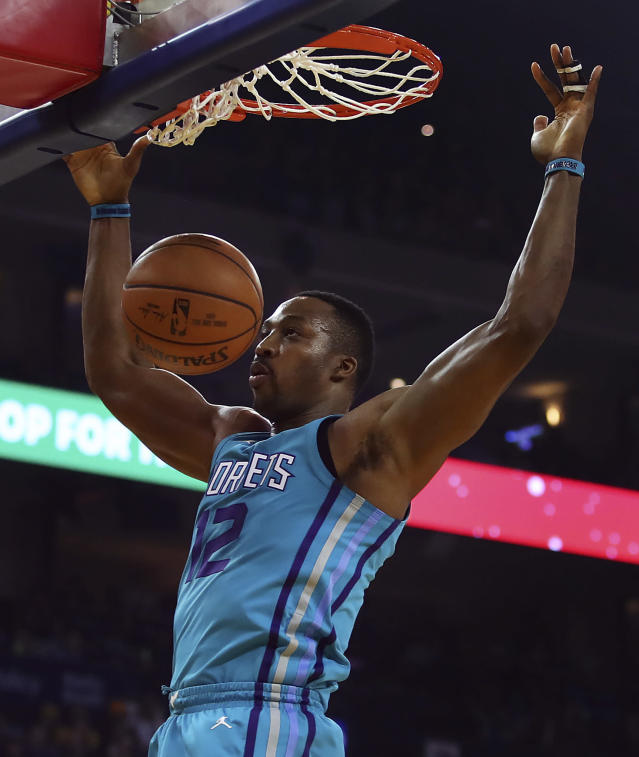 FILE - In this Dec. 29, 2017, file photo, Charlotte Hornets' Dwight Howard scores against the Golden State Warriors during the first half of an NBA basketball game, in Oakland, Calif. A person familiar with the situation says the Charlotte Hornets have agreed to trade eight-time All-Star center Dwight Howard to the Brooklyn Nets for center Timofey Mozgov and two future second-round draft picks. The person spoke to The Associated Press on condition of anonymity Wednesday, June 20, 2018, because the teams have not announced the trade and the league has not yet approved it. (AP Photo/Ben Margot, File)