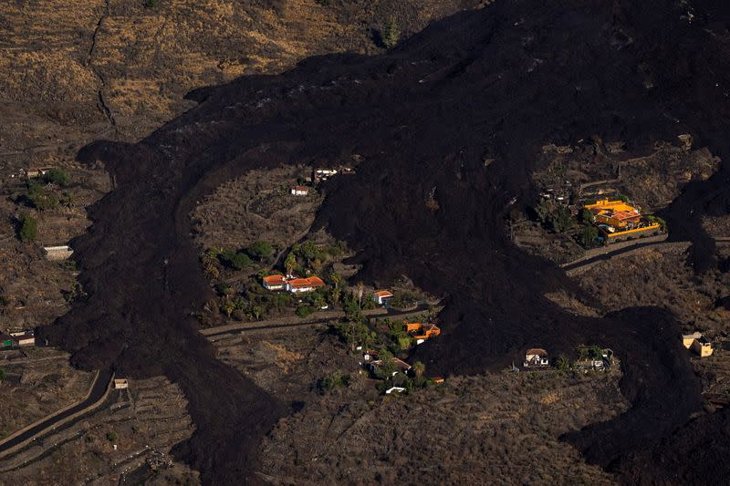 Lava flows around houses following the eruption of a volcano on the Island of La Palma