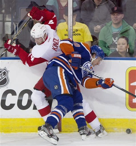 Detroit Red Wings' Jakub Kindl (4) is checked by Edmonton Oilers' Shawn Horcoff (10) during the first period of an NHL hockey game Friday, March 15, 2013, in Edmonton, Alberta. (AP Photo/The Canadian Press, Jason Franson)