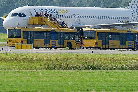 Passengers leave a Vueling plane which is parked at a field near Amsterdam Airport after a hijack scare August 29, 2012.
