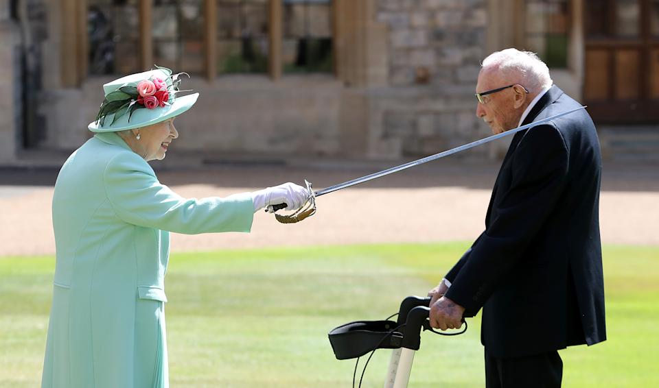 WINDSOR, ENGLAND - JULY 17: Queen Elizabeth II awards Captain Sir Thomas Moore with the insignia of Knight Bachelor at Windsor Castle on July 17, 2020 in Windsor, England. British World War II veteran Captain Tom Moore raised over £32 million for the NHS during the coronavirus pandemic.  (Photo by Chris Jackson/Getty Images)