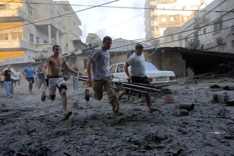 FILE PHOTO: Lebanese men run to help survivors after an Israeli bombing destroyed two six-storey high buildings in Tyre