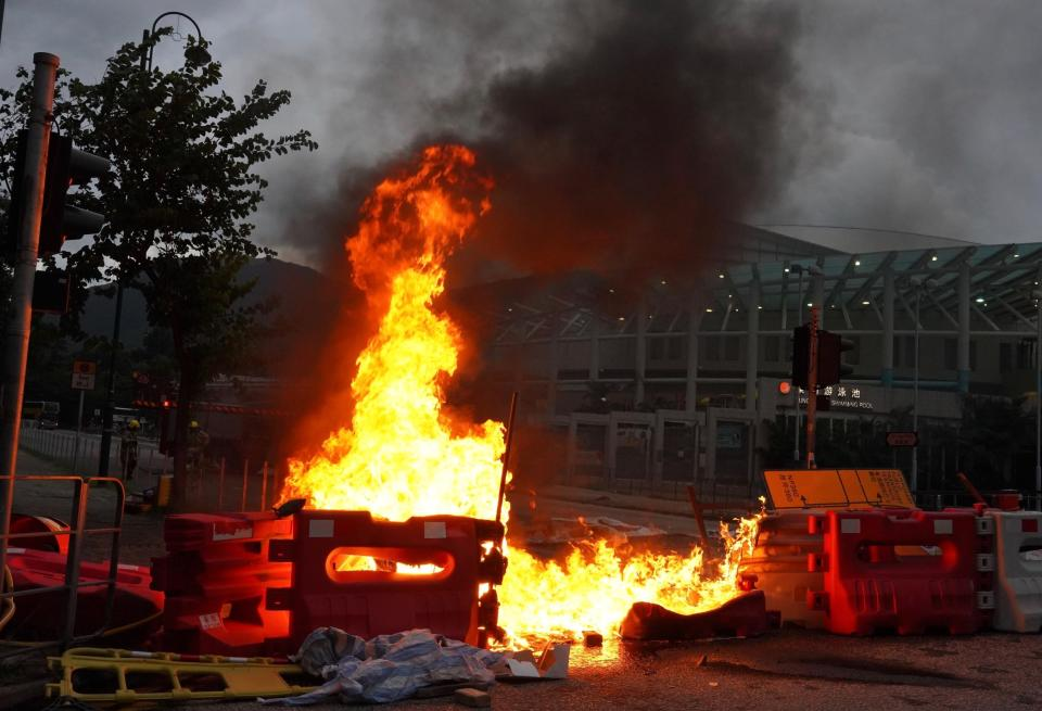 Protesters set fire to road barriers at Tung Chung near airport in Hong Kong, Sunday, Sept.1, 2019. Train service to Hong Kong's airport was suspended Sunday as pro-democracy demonstrators gathered there, while protesters outside the British Consulate called on London to grant citizenship to people born in the former colony before its return to China. (AP Photo/Vincent Yu)
