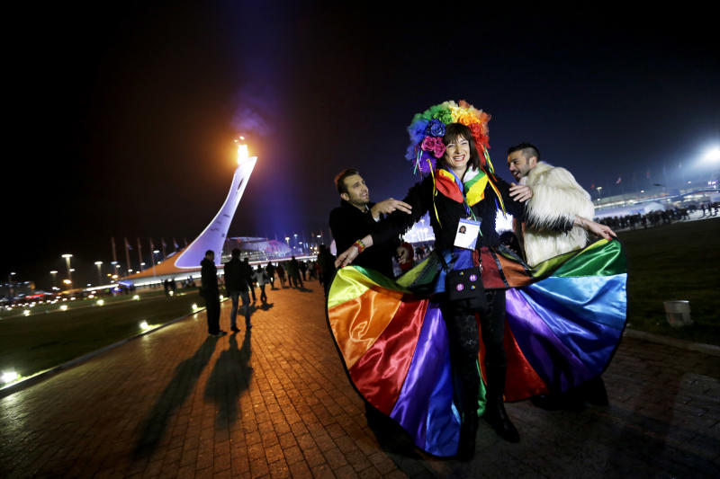 Vladimir Luxuria, center, a former Communist lawmaker in the Italian parliament and prominent crusader for transgender rights, is led away by friends to attend a women's ice hockey match after posing for photos on the Olympic Plaza at the 2014 Winter Olympics, Monday, Feb. 17, 2014, in Sochi, Russia. Luxuria was soon after detained by police upon entering the Shayba Arena. (AP Photo/David Goldman)