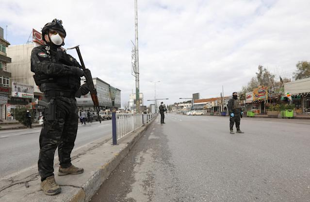 Security men stand in an empty street during a curfew imposed by Iraqi Kurdish authorities, following the outbreak of coronavirus, in Sulaimaniya, in Iraqi Kurdistan, lraq. (Reuters)