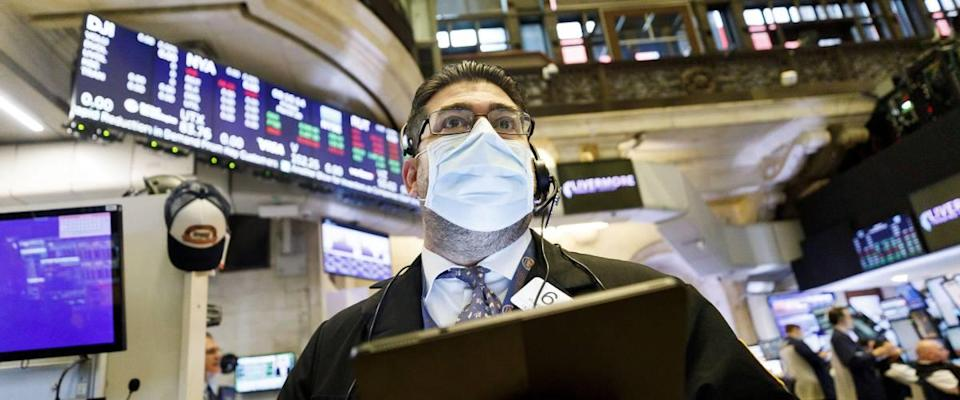Man wearing face mask at New York Stock Exchange, holding tablet