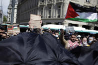 A protester holds a Palestinian flag in Paris, Saturday, May 22, 2021, as they take part in a rally supporting Palestinians. Egyptian mediators held talks Saturday to firm up an Israel-Hamas cease-fire as Palestinians in the Hamas-ruled Gaza Strip began to assess the damage from 11 days of intense Israeli bombardment.Supporters of the Palestinians. (AP Photo/Thibault Camus)