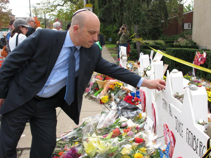 "FILE - In this Wednesday, Oct. 31, 2018, file photo, Jonathan Greenblatt, CEO and national director of the Anti-Defamation League, places a stone on the Star of David for Dr. Jerry Rabinowitz at Tree of Life synagogue in Pittsburgh. Greenblatt flew in for the funerals of victims of the fatal mass shooting at the synagogue. ""It's clear we must remain vigilant in working to counter the threat of violent anti-Semitism and denounce it in all forms, wherever the source and regardless of the political affiliation of its proponents,"" said Greenblatt. (AP Photo/Allen G. Breed, File)"