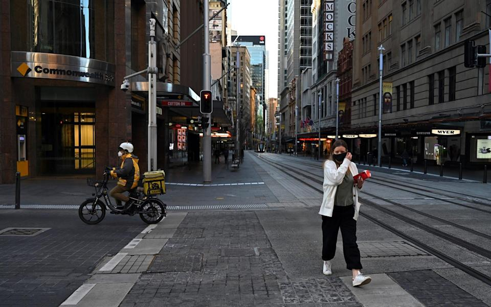 A woman crosses the street as a delivery rider drives past in the Sydney CBD, Australia on September 16, 2021. ( - Anadolu