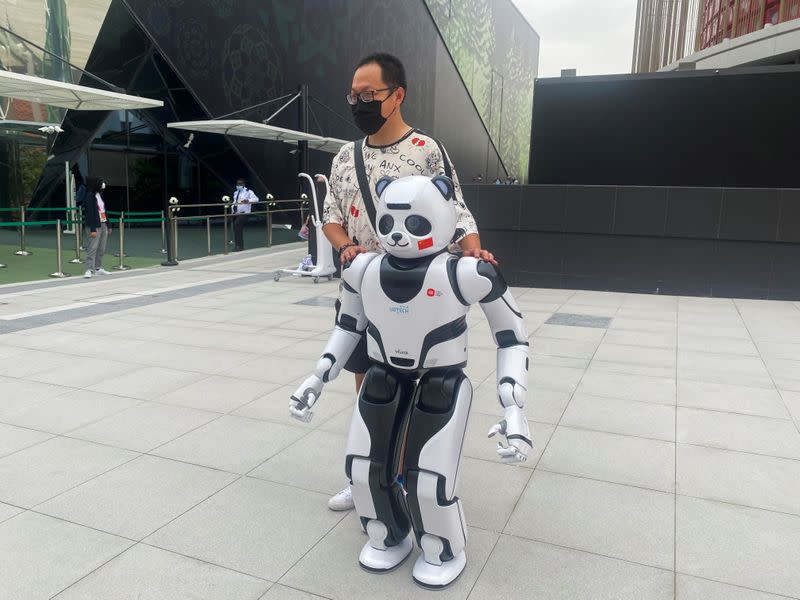 A man stands next to a panda robot at the Chinese Pavilion at the Expo 2020 in Dubai