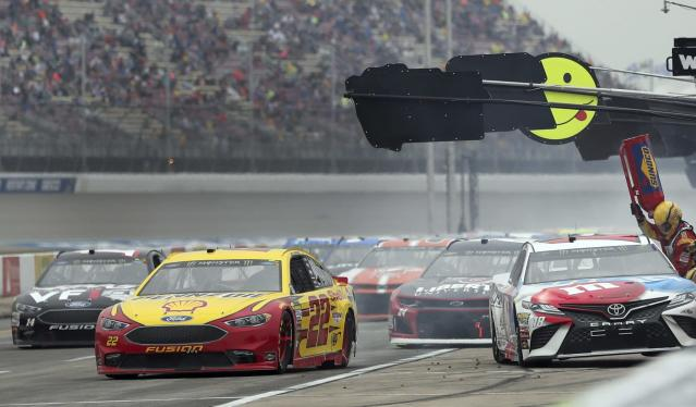 """<a class=""""link rapid-noclick-resp"""" href=""""/nascar/sprint/drivers/1542/"""" data-ylk=""""slk:Joey Logano"""">Joey Logano</a> (22) pulls away from his pit stop during a NASCAR Cup Series auto race, Sunday, June 10, 2018, in Brooklyn, Mich. (AP Photo/Carlos Osorio)"""
