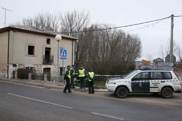 Spanish Gardia Civil stand near burntout house where six people died in a house fire in Tordomar, near Burgos on February 22, 2014. Three adults aged between 35 and 59 as well as three young boys aged four and six perished in the early morning blaze that also wounded five other occupants of the house at the cottage in the Ribera del Arlanza Tordomar where two others managed to escape the flames.        (Photo credit should read CESAR MANSO/AFP/Getty Images)