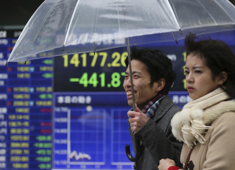 People walk by an electronic stock board of a securities firm in Tokyo, Tuesday, Feb. 4, 2014. Weakness in U.S. and Chinese manufacturing sent Asian stock markets sharply lower Tuesday. (AP Photo/Koji Sasahara)