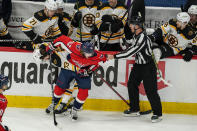 Boston Bruins defenseman Charlie McAvoy (73) and Washington Capitals left wing Carl Hagelin (62) try to get untangled with the help of linesman Devin Berg (87) during the second period of Game 2 of an NHL hockey Stanley Cup first-round playoff series Monday, May 17, 2021, in Washington. (AP Photo/Alex Brandon)
