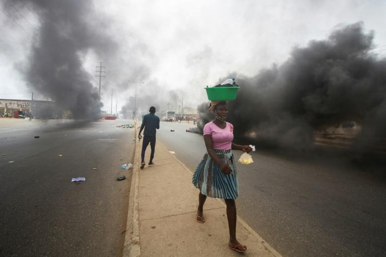 A street vendor walks past smoke from burning tyres during a anti-government demonstration in Luanda on October 24, 2020
