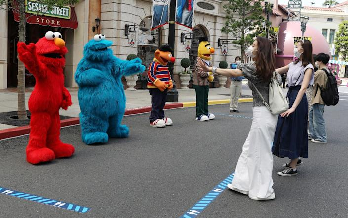 Sesame Street characters demonstrating how to greet visitors while keeping social distancing guidelines - AFP