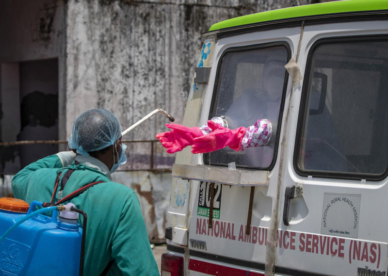 A health worker sprays disinfectant on the gloves of a doctor sitting inside a van to collect samples from people to be tested for the coronavirus in Dharmsala, India, Saturday, May 9, 2020. India relaxed some coronavirus lockdown restrictions on Monday even as the pace of infection picked up and reopenings drew crowds of people. (AP Photo/Ashwini Bhatia)