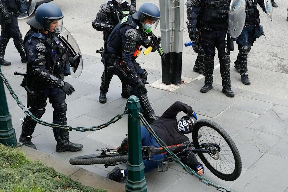 A demonstrator is handled by police officers attempting to disperse a protest against Covid-19 regulations in Melbourne on 21 September 2021 (AFP via Getty Images)