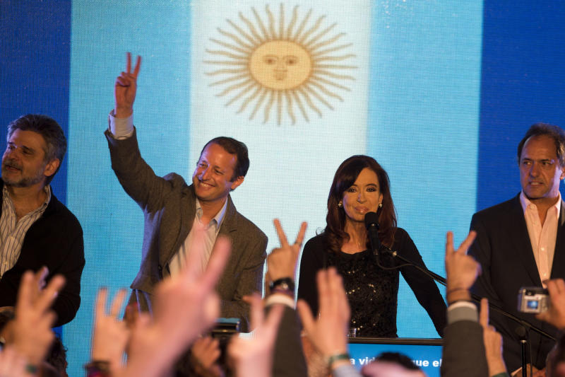 CORRECTS DATE TO SUNDAY, AUG. 11, 2013 - Argentine President Cristina Fernandez, second right, looks at supporters who flash the victory sign next to candidate Martin Insaurralde, second from left, and Buenos Aires state governor Daniel Scioli, right, before giving a speech regarding the election results in Buenos Aires, Argentina, Sunday, Aug. 11, 2013. Argentines went to the polls in a nationwide mandatory primaries to select candidates for the Oct. 27 midterm election for legislators and senators. (AP Photo/Victor R. Caivano)