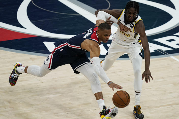 Washington Wizards guard Russell Westbrook (4) gets past Indiana Pacers guard Justin Holiday (8) during the second half of a basketball game, Monday, May 3, 2021, in Washington. (AP Photo/Alex Brandon)