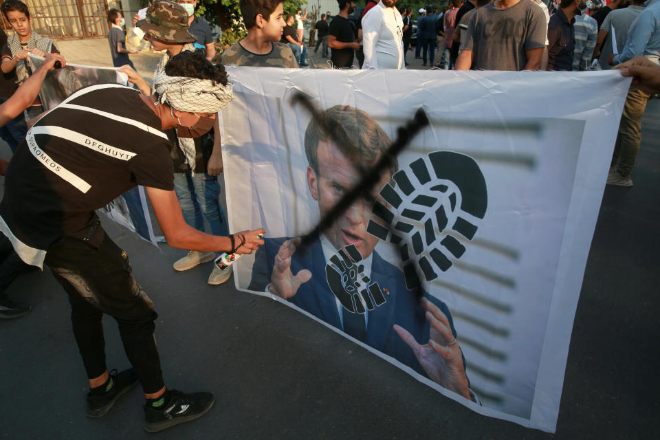 Protesters deface a picture of French President Emmanuel Macron during a protest over caricatures of the Prophet Muhammad they deem insulting and blasphemous, outside the French Embassy, in Baghdad, Iraq, Monday, Oct. 26, 2020. Muslims in the Middle East and beyond on Monday called for boycotts of French products and for protests over the caricatures, but France's president has vowed his country will not back down from its secular ideals and defense of free speech. (AP Photo/Khalid Mohammed)