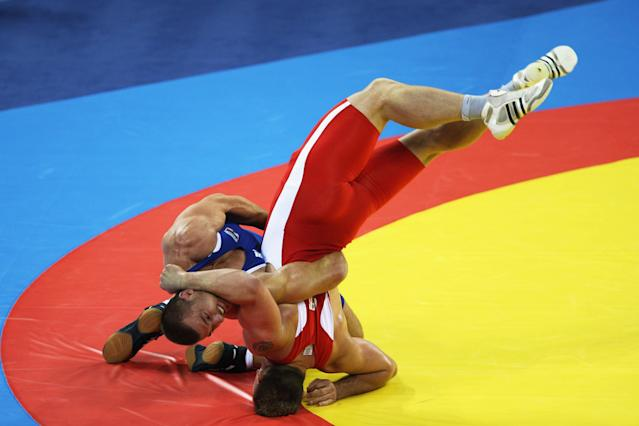 BEIJING - AUGUST 14: Mirko Englich (red) of Germany is thrown by Elis Guri (blue) of Albania in the Men's Greco-Roman 96kg quarter final bout at the China Agriculture University Gymnasium during Day 6 of the Beijing 2008 Olympic Games on August 14, 2008 in Beijing, China. (Photo by Ezra Shaw/Getty Images)