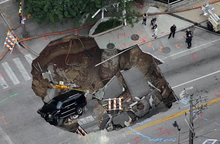 A Cadillac Escalade sits at the bottom of a sinkhole in Milwaukee, Wis. on Friday, July 23, 2010, still running almost 20 hours after the driver fell in. On Thursday, powerful storms pounded southeastern Wisconsin and caused widespread flooding. (AP Photo/Mark Was)
