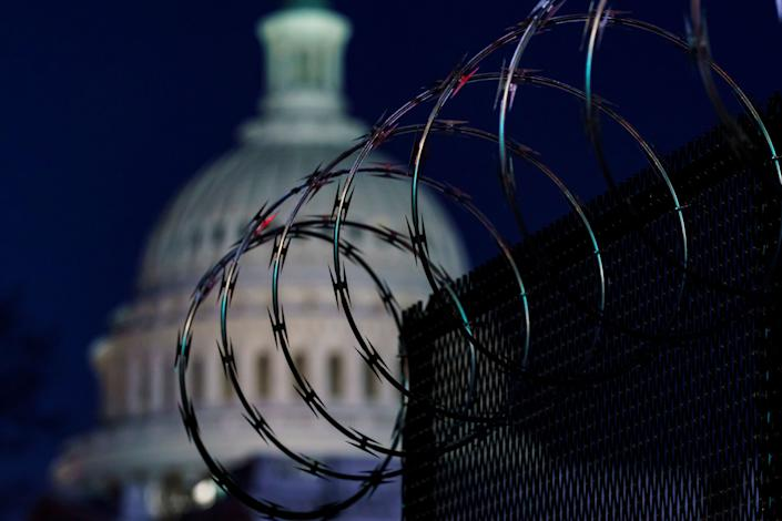 Riot fencing and razor wire reinforce the security zone on Capitol Hill in Washington on Tuesday, the day before Joe Biden's inauguration. (Photo: J. Scott Applewhite/Associated Press)