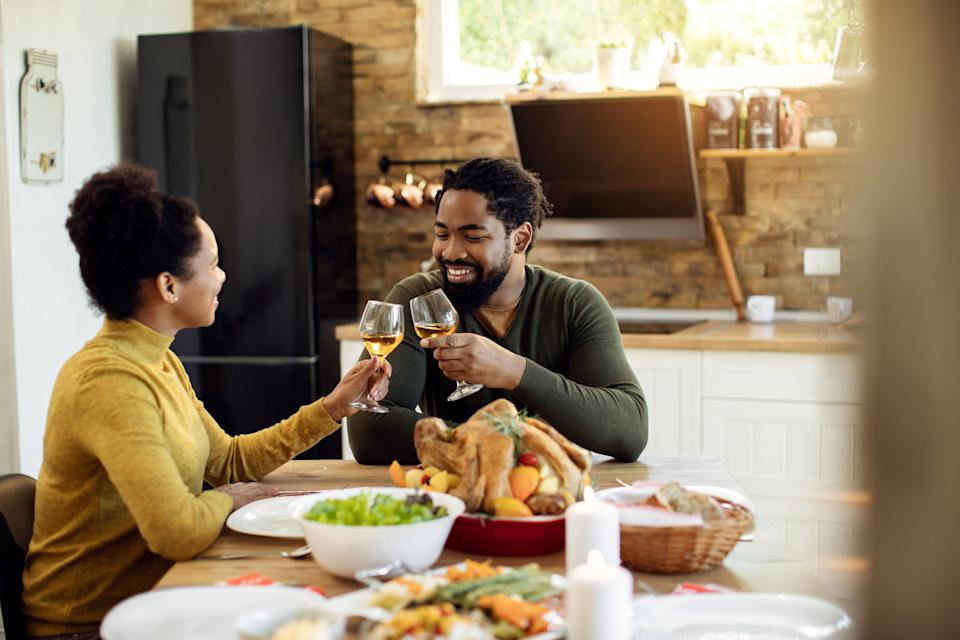 Happy black couple tasting with wine while having Thanksgiving lunch at dining table.