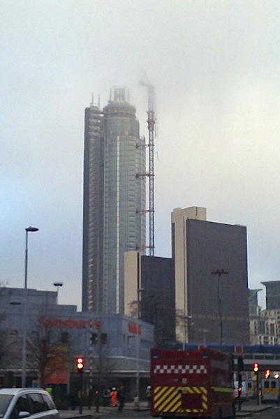 A general view of emergency vehicles as they approach the site of a helicopter crash in central London, and showing damage to a crane on the side of St. George's Tower, in background, which the helicopter is thought to have crashed into before falling to ground, Wednesday Jan. 16, 2013. A helicopter has crashed during rush hour in central London after apparently hitting a construction crane on top of a building, police said. (AP Photo / Sarah Grun, PA) UNITED KINGDOM OUT - NO SALES - NO ARCHIVES