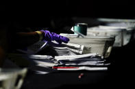 Election personnel handle ballots as vote counting in the general election continues at State Farm Arena, Wednesday, Nov. 4, 2020, in Atlanta. (AP Photo/Brynn Anderson)