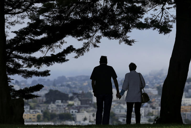 FILE - In this July 3, 2017 file photo, a man and woman walk under trees down a path at Alta Plaza Park in San Francisco. Data from the U.S. Census Bureau shows the median age in the U.S has increased by a year to 38.2 years from 2010 to 2018. The date released Thursday, June 20, 2019, comes as many baby boomers have been hitting the retirement age in recent years. (AP Photo/Jeff Chiu, File)