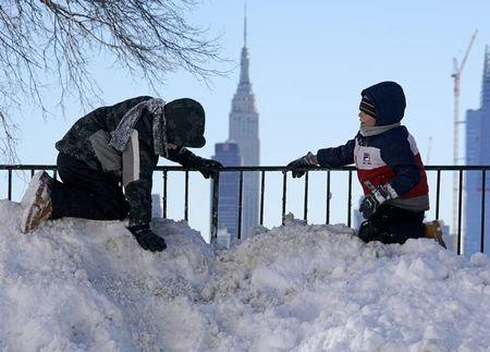 Two boys play atop a pile of snow at the end of a street in Union City