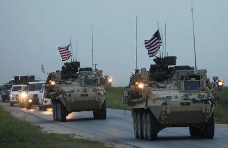 U.S military vehicles and Kurdish fighters from the People's Protection Units (YPG) drive in the town of Darbasiya next to the Turkish border